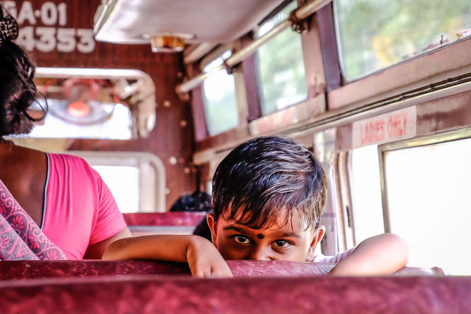 Little Indian boy staring on bus