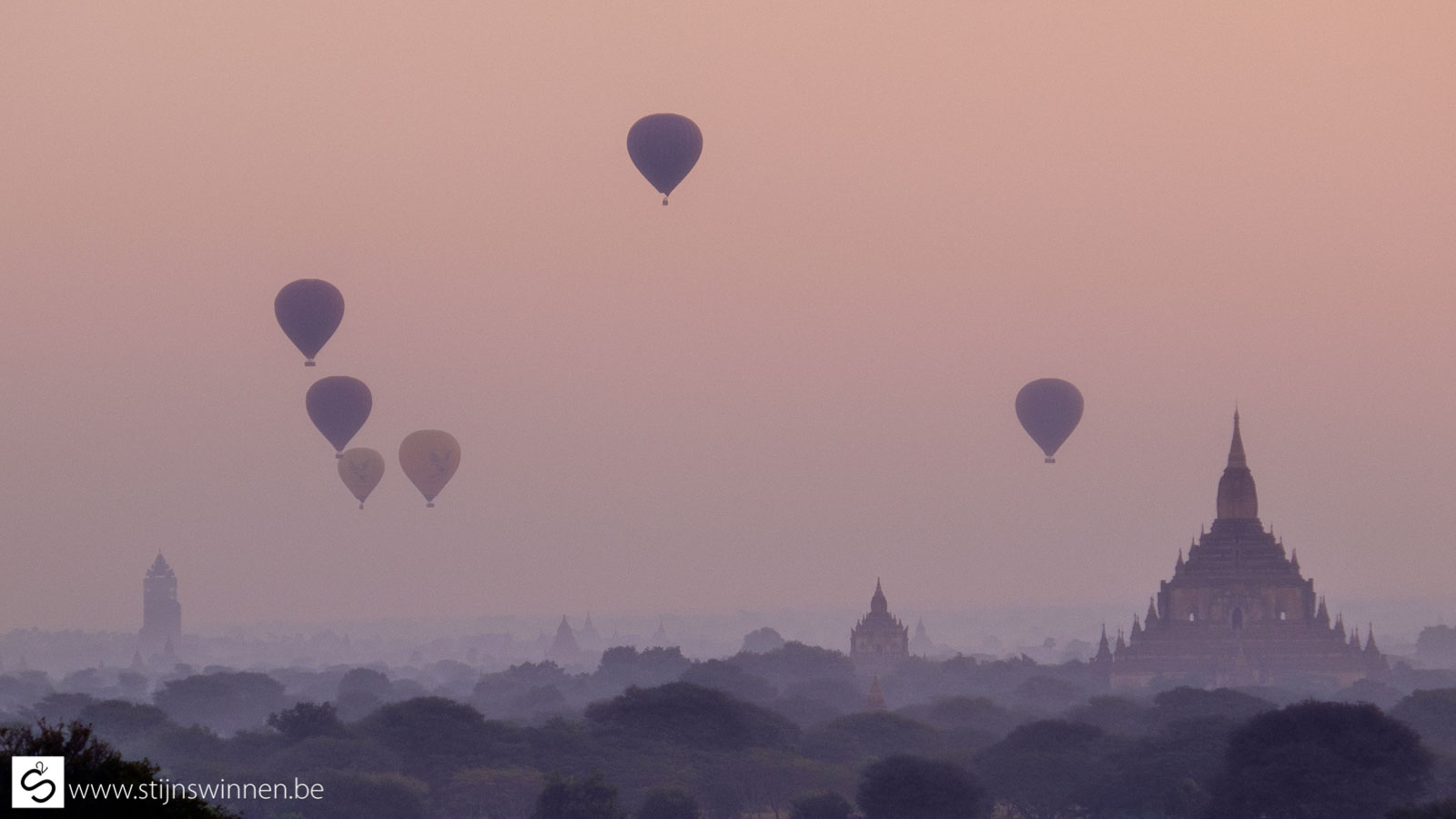 Pagoda in Bagan at sunrise with many balloons
