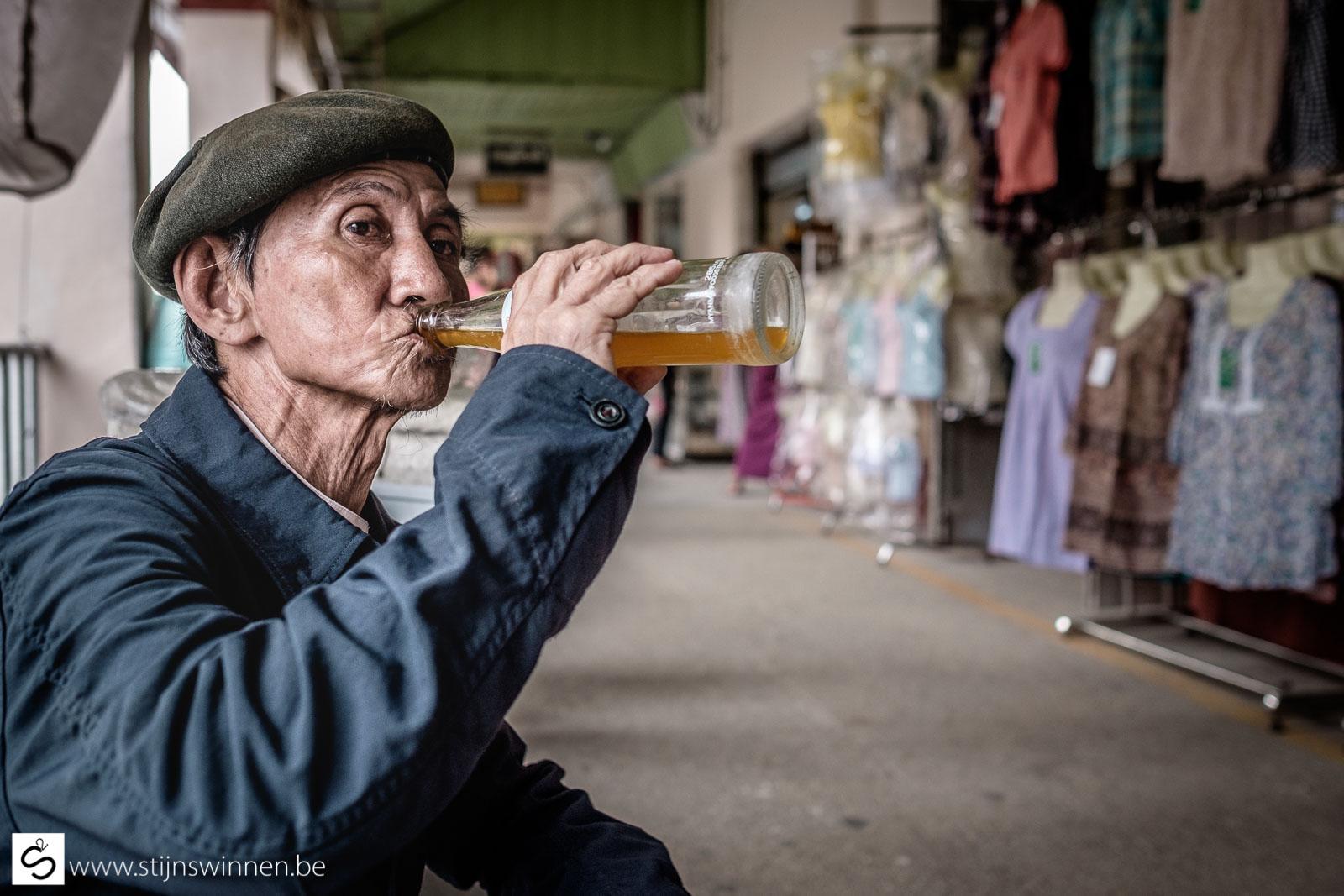 Old Burmese man drinking a soft drink on market in Yangon