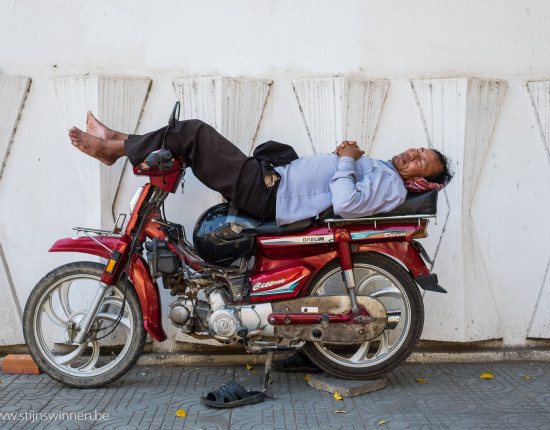 Man sleeping on a bike in Phnom Penh, Cambodia