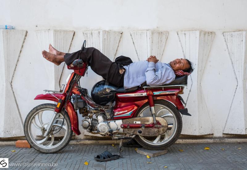 Man sleeping on a bike in Phnom Penh, Cambodia